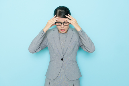 beauty elegant lawyer woman having working problem and feeling uncomfortable because she getting headache isolated on blue background.