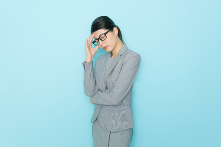professional pretty business woman feeling tired in blue wall background and getting headache when she working long time.
