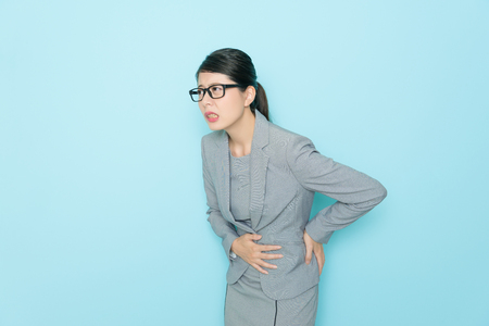 beautiful sweet suit women having stomachache disease and working long time getting waist painful isolated blue wall background.