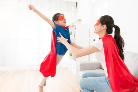 かわいい女の子を抱いているかなり若い母親が飛ぶポーズを作り、自宅でスーパーヒーローとしてプレーします。