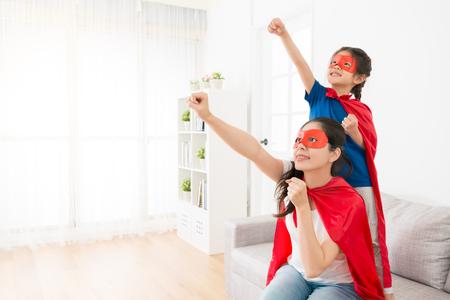 gelukkige moeder met kleine dochter op bank in de woonkamer spelen als superheld samen en het maken van dezelfde poseren klaar om te vliegen op vakantie ontspannen tijd.