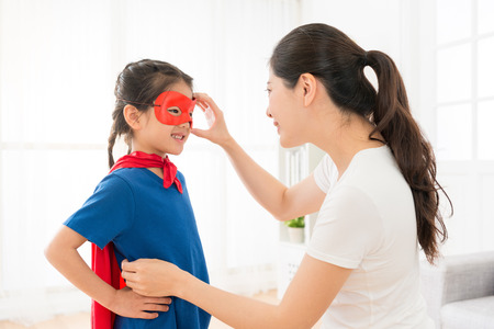 beautiful sweet girl kid wearing red cloak play as superhero and elegant young mother helping her adjusting mask in living room at home.