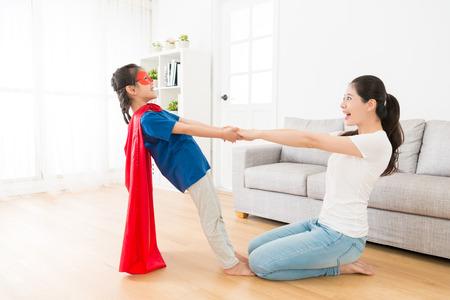 Glückliches hübsches Kindermädchen, das Superheldkleidung mit schöner fröhlicher Mutter Hand in Hand zu Hause trägt, lustige Zeit genießend. Standard-Bild - 89352971