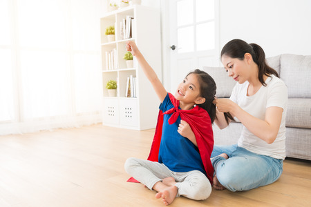 happy cute little kid daughter wearing red cloak play as superhero and making ready to fly posing sitting on living room wooden floor when her mother helping tied hair.