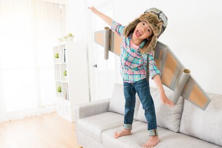 Felici bambini femminili allegri guardando fotocamera ridendo e indossando costume astronauta facendo volare posa in piedi sul divano divano godendo il tempo di gioco. Archivio Fotografico - 88694322