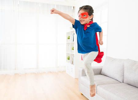 attractive sweet little girl jumping from sofa couch to fly when she play as superhero with cloak and mask at home in living room.