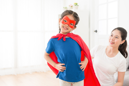 youth beautiful little kid girl face to camera wearing red cloak with mask play as superhero and beauty smiling mother looking at her.