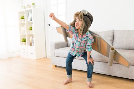 自宅でリビングルームの木製の床に立ってジェスチャーを飛ぶために準備ができている宇宙飛行士の衣装を着て笑顔甘い女の子。