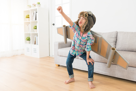 beautiful young little girl children standing on living room floor showing fly posing and wearing wings decoration play as astronaut.