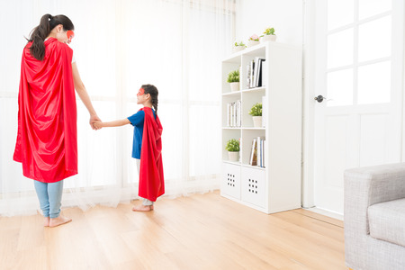 back view photo of happy mother and little daughter wearing red cloak with mask looking each other playing as superhero standing in front of living room window.