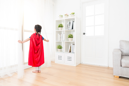 back view photo of youth lovely little girl children playing as superhero and standing on living room wooden floor opening curtain looking at window. Banque d'images