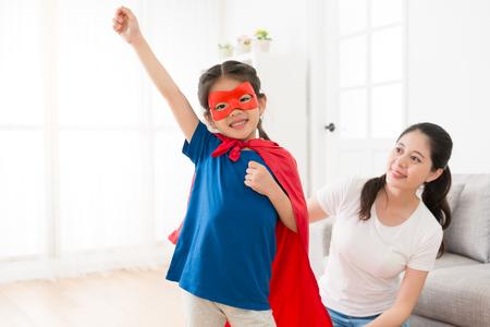 glückliches reizendes kleines Mädchen, welches die Superheldkleidung trägt, die bereit ist zu fliegen, die Kamera lächelnd im Wohnzimmer mit schöner junger Mutter zu fliegen.