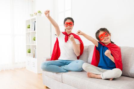 同じスーパー ヒーローとしてカメラと再生するソファ ソファの顔の上に座って若い可愛い娘と笑顔のかわいい母は、飛ぶ準備ができてポーズ。
