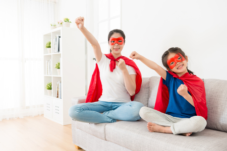 smiling pretty mother with lovely young little daughter sitting on sofa couch face to camera and play as superhero making same posing ready to fly.