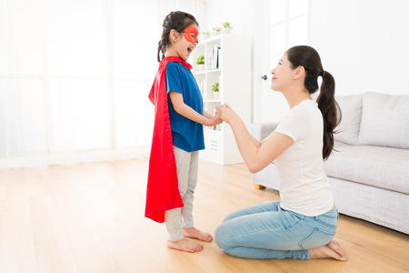 smiling young mother holding happy lovely little daughter hand and looking each other in living room at home when girl play as superhero.