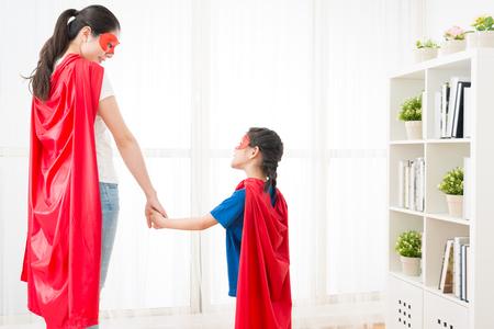 お互いを見て、夏の休暇で家で一緒にスーパー ヒーローとして遊んで素敵な女の子で笑顔の女性のクローズ アップ写真。