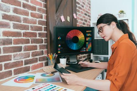 Trabajadora de oficina atractiva de la belleza que hace trabajo del diseño gráfico con la pluma digital del cojín y que usa la computadora móvil que busca la nueva idea Foto de archivo