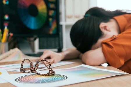 セレクティブ フォーカス設計グラフィック製品長時間疲れやオフィスの机の上に睡眠を感じて若いきれいな女性事務員の写真。