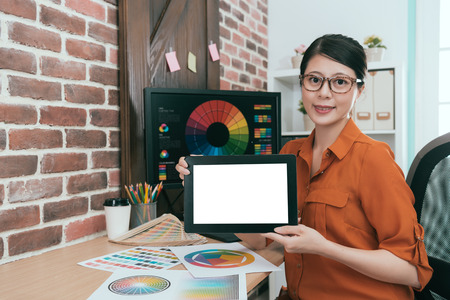 beautiful confident woman designer holding mobile digital tablet pad showing blank screen and looking at camera smiling when she working in design office.