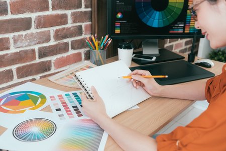 smiling professional woman artist using pencil drawing graph with many color paper to design new season product of company.