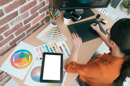 a foto da opinião de ângulo alto do desenhista gráfico fêmea atrativo novo que usa o projeto digital do desenho da pena da almofada da tecnologia trabalha e mostrando a tela vazia do computador móvel.