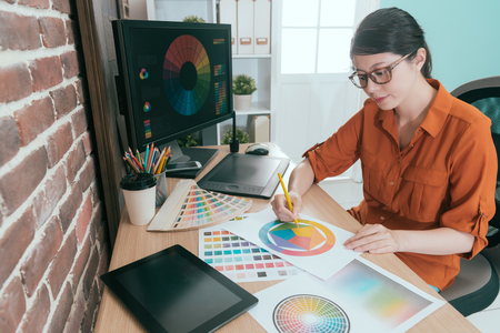 professional young female graphic designer choosing design color in office. 스톡 콘텐츠