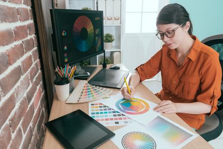 diseñador gráfico femenino joven profesional que elige color del diseño en oficina. Foto de archivo