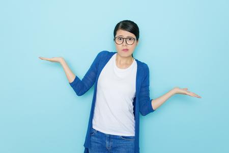 unglückliche junge Frau, die das Wählen von Stellung stehend im blauen Wandhintergrund und Betrachten der Kamera zeigt verwirrtes emotionales Gesicht zeigt.