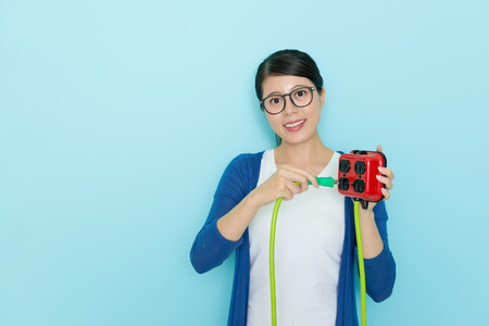 smiling happy woman using plug pull out socket showing saving electric concept isolated on blue wall background with lifestyle clothing.