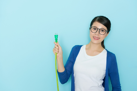 smiling pretty lady face to camera standing in blue wall background and holding plug line device showing saving electric concept.