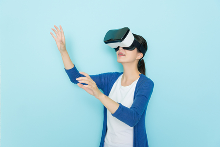 smiling young woman in virtual reality glasses standing in blue wall background and wearing lifestyle clothing using hands playing 3D online game.