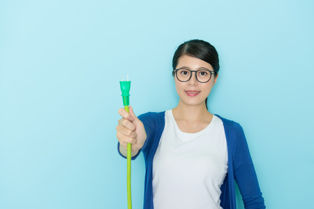 beautiful confident girl showing plug line equipment looking at camera smiling and standing in blue background wearing lifestyle clothing with selective focus photo.