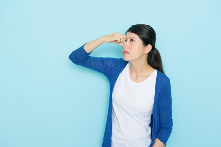 아름 다운 젊은 여자 냄새 파란색 배경에 고립 코 닫는 손을 사용 하여 나쁜 냄새.
