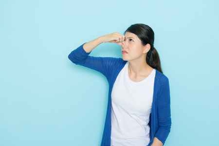 beautiful young woman smelling bad odor using hands closing nose isolated on blue background. Archivio Fotografico