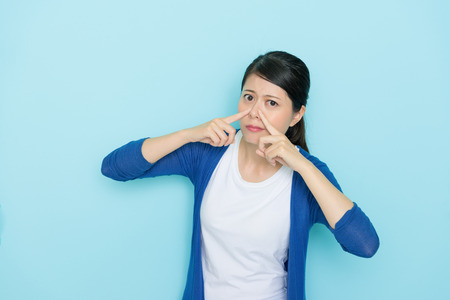 elegant young girl using hands pressed nose looking at camera when she smelling bad taste isolated on blue wall background. Stock Photo