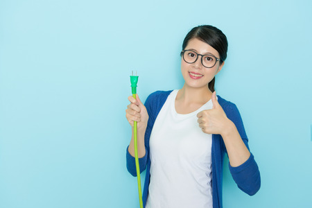 happy confident woman holding plug showing save electric concept and wearing lifestyle clothing making thumb up gesture standing in blue background.