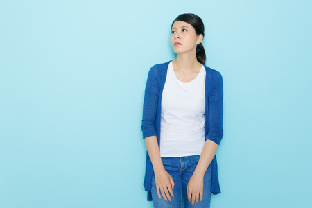unhappy sad female teenager standing in blue background daydreaming when she break up losing love feeling depressed and sorrow.