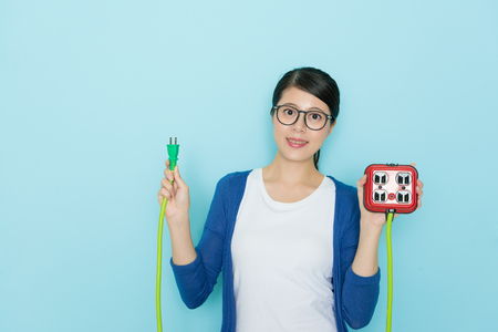 attractive young lady showing plug with socket standing in blue background and wearing lifestyle freedom clothing looking at camera smiling.