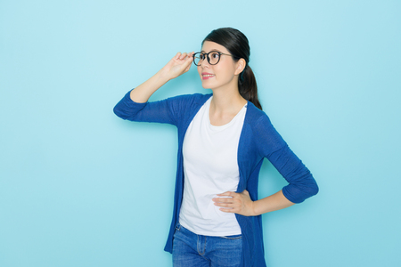 fantasize: happy pretty female student standing in blue wall background and holding glasses looking at distance thinking future plan.