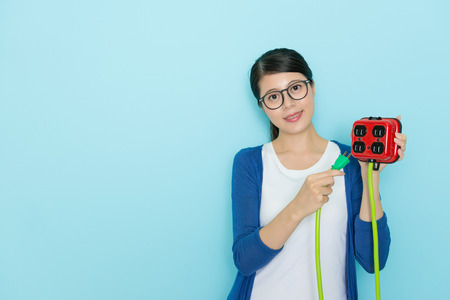 smiling sweet woman wearing lifestyle clothing holding electricity device face to camera and showing saving electric concept standing in blue background.