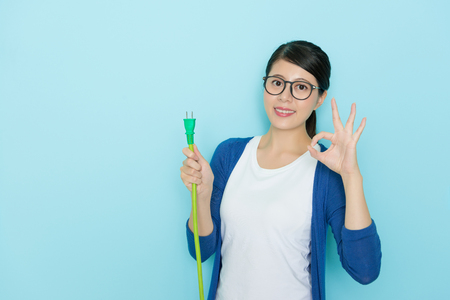 young beauty woman face to camera making okay gesture standing in blue background and holding plug line device showing save electric concept. Stock Photo