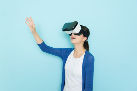 happy pretty woman wearing VR device headset equipment browsing online shopping website in blue background and making grab gesture looking for goods.