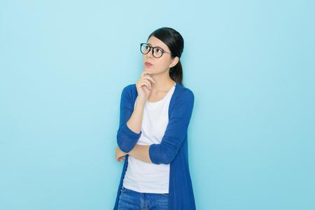 Chica muy elegante que tiene problemas para sentirse confundido y mirando la solución de pensamiento de área vacía aislada sobre fondo azul.