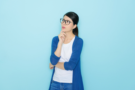 mooie elegante meid met probleem gevoel verward en kijken naar leeg gebied denken oplossing geïsoleerd op blauwe achtergrond.