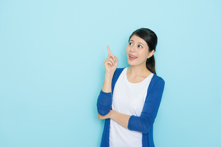 pretty beauty girl student having good idea about future plan and showing pointing gesture looking at empty area isolated on blue background.