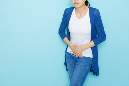 sad unhappy woman using hands touching belly position when she feeling painful suffering during menstruation period isolated on blue background.