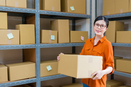 beautiful pretty female office worker holding big online shopping box parcel standing in warehouse face to camera.