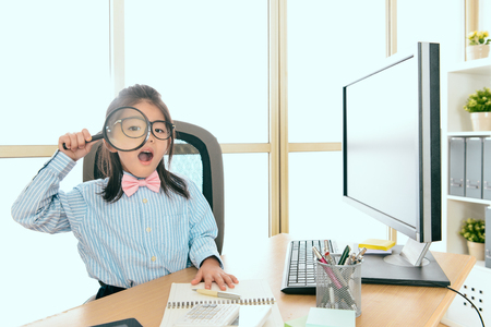 cute beautiful little girl dressed up as business worker sitting in personal workplace and using magnifier tool looking at camera.