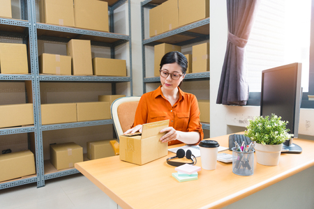 professional young female online shopping owner sitting in warehouse office workplace area and packing order parcel box preparing to ship for customer.