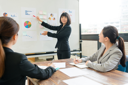 junge schöne geschäftsfrau präsentiert neue corporation fallplan für alle partner auf whiteboard während firmensitzung Standard-Bild